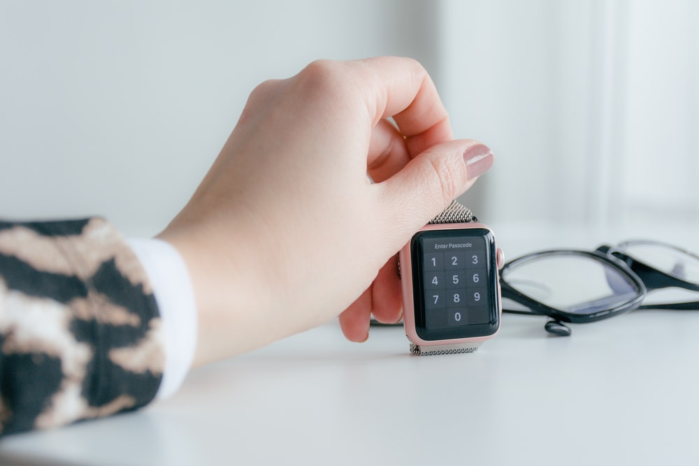 person holding gold-colored smartwatch