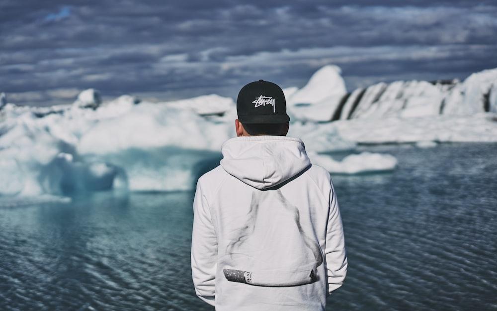 man wearing white pullover hoodie facing glaciers