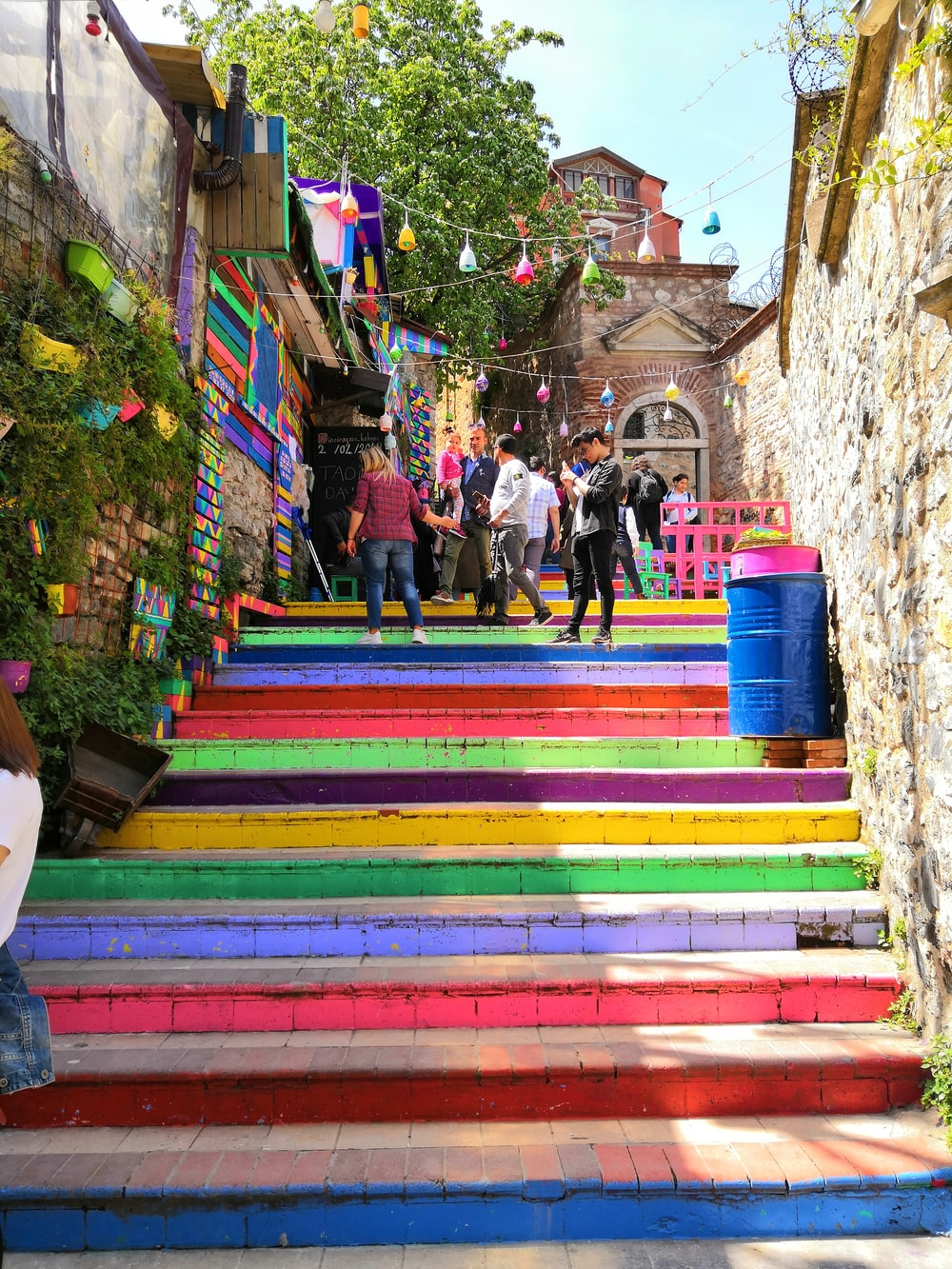 people walking climbing on multicolored stairs