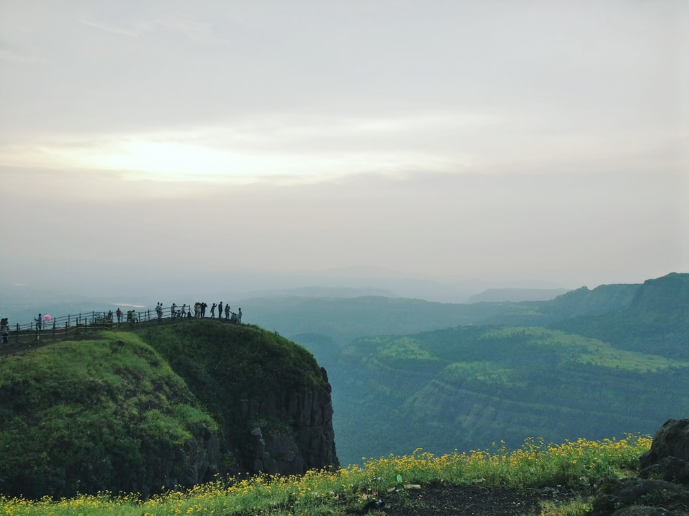 people standing on cliff