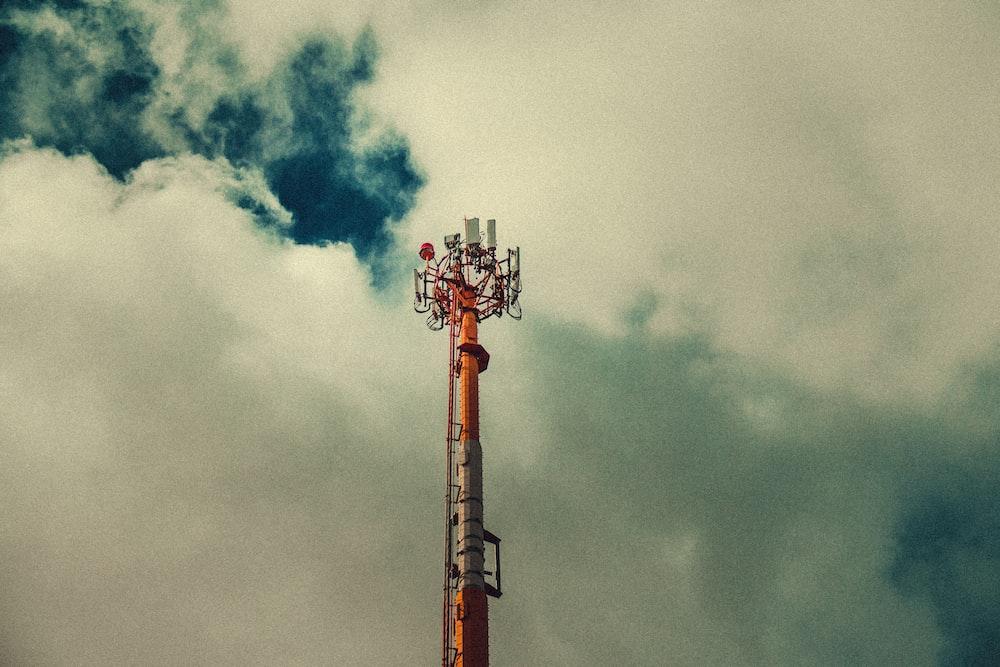 orange and white tower under white skies