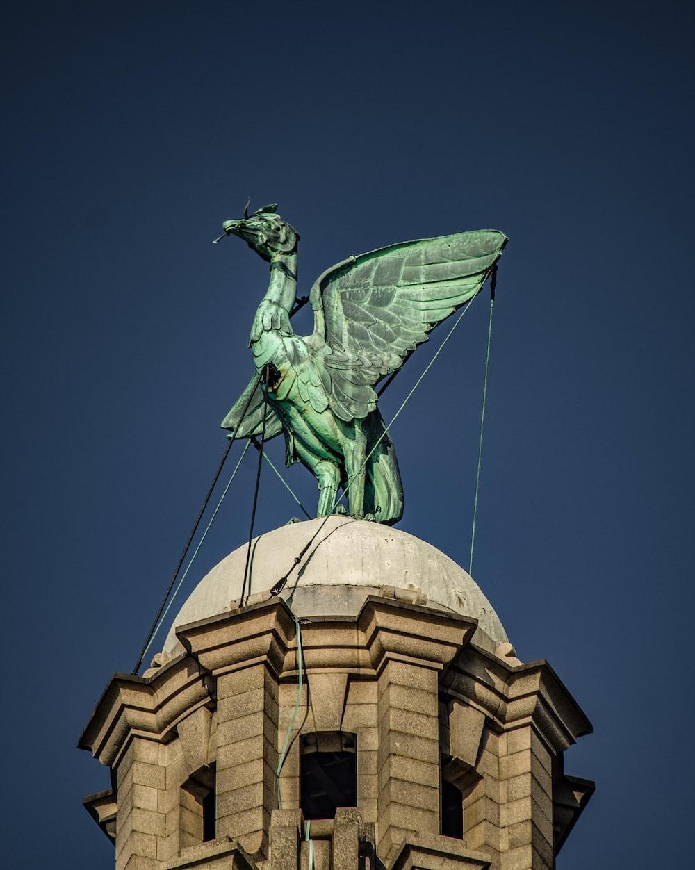 green bird statue above temple