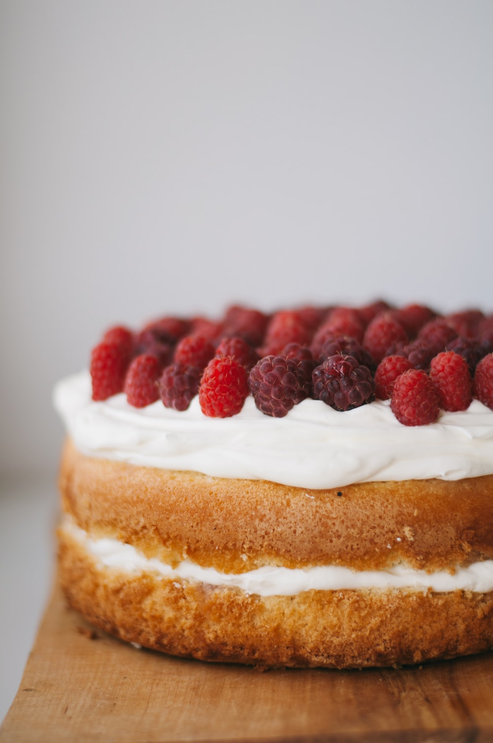 round cake with white frosting topped with red raspberries