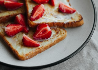 plate of toasted breads topped with sliced strawberries