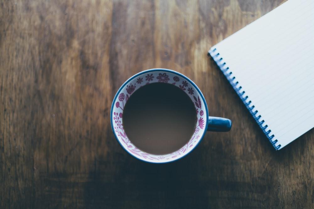 chocolate drink in mug near blue spiral notebook