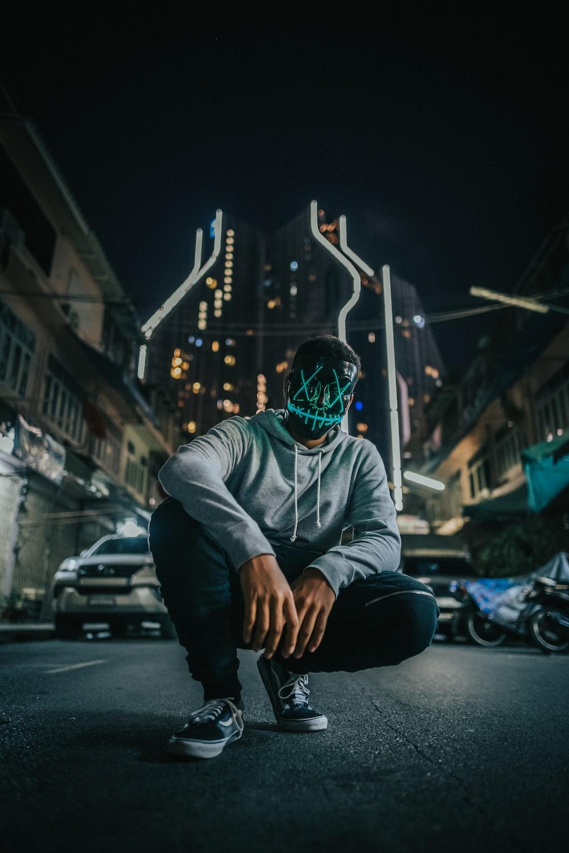 man in grey hoodie wearing black and green mask