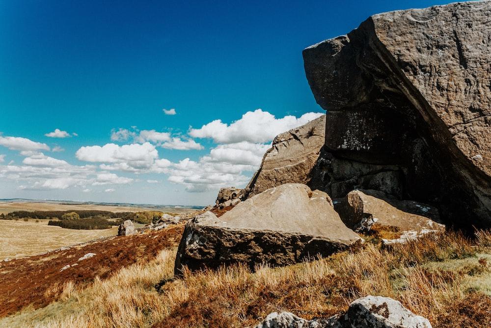 boulders on hill under blue sky