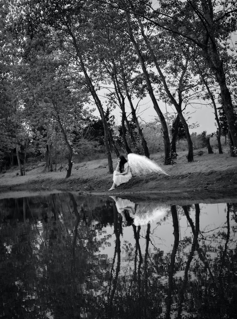 grayscale photography of female angel sitting beside body of water