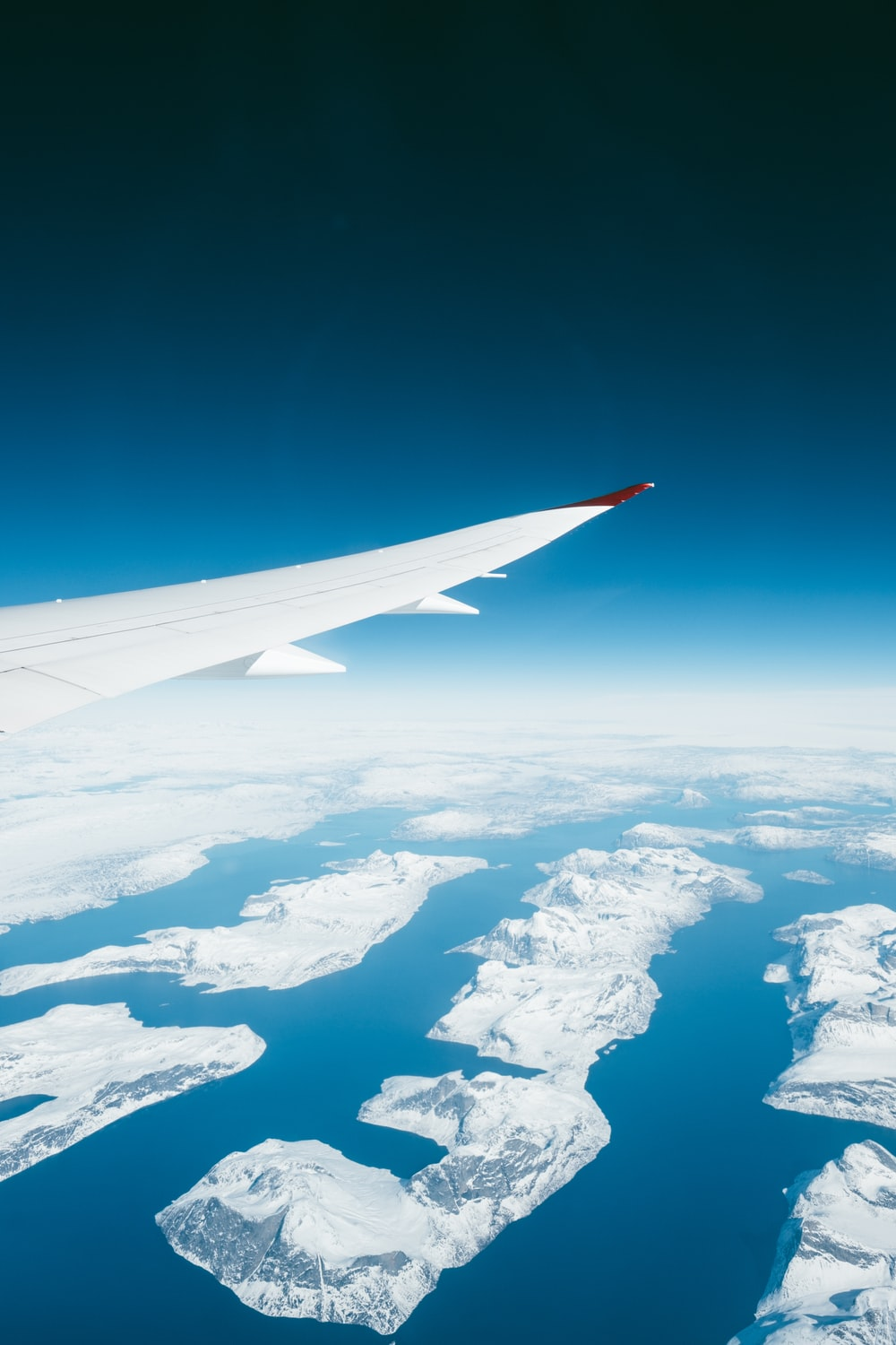 white airplane over rock mountains and blue sea
