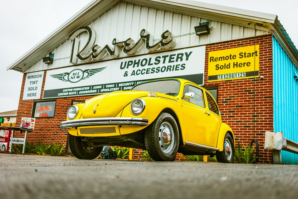 yellow Volkswagen Beetle parked Revere upholstery and accessory shop