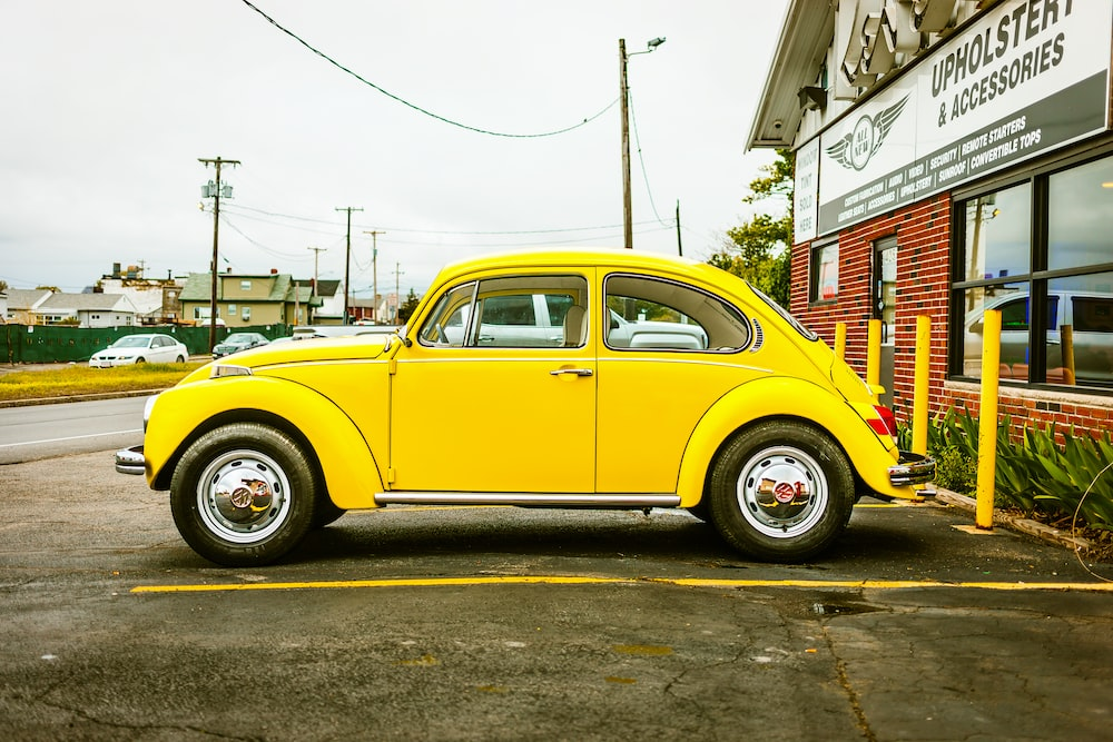 yellow Volkswagen Beetle coupe parked near building