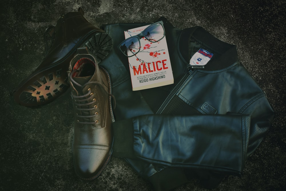 pair of brown boots beside jacket