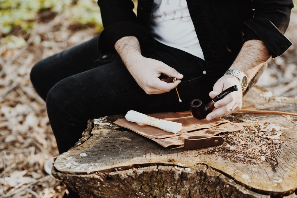 man holding tobacco while sitting on wood slab