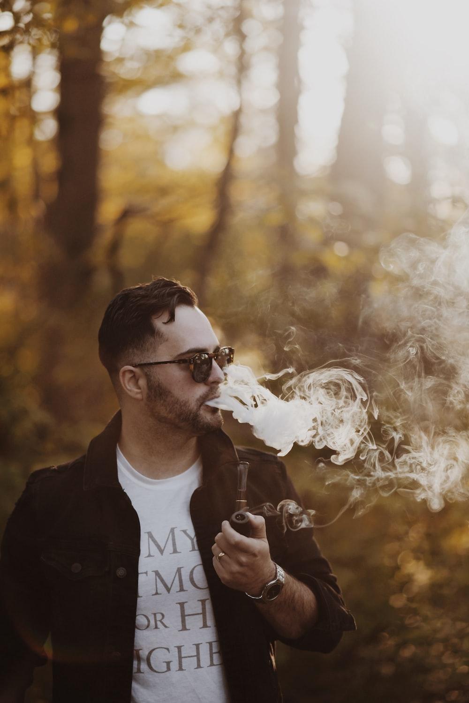 man wearing black jacket holding smoking pipe