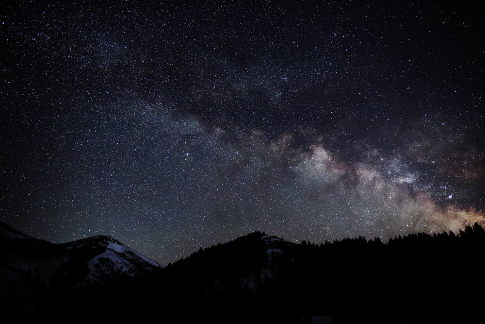 silhouette of mountain during starry night