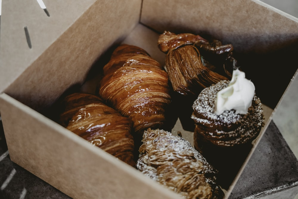 five croissants in brown box
