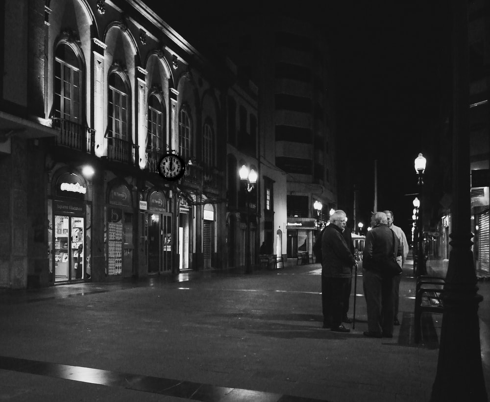 grayscale photography of people standing near building