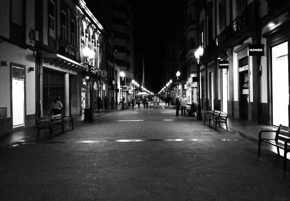 grayscale photo of street between lighted buildings