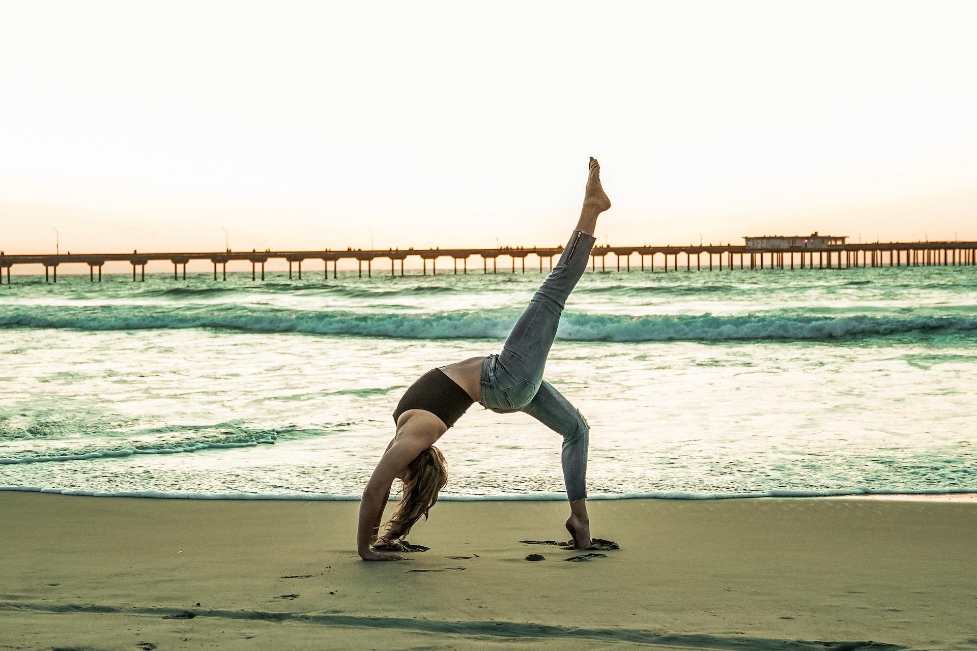 woman doing yoga pose on seashore