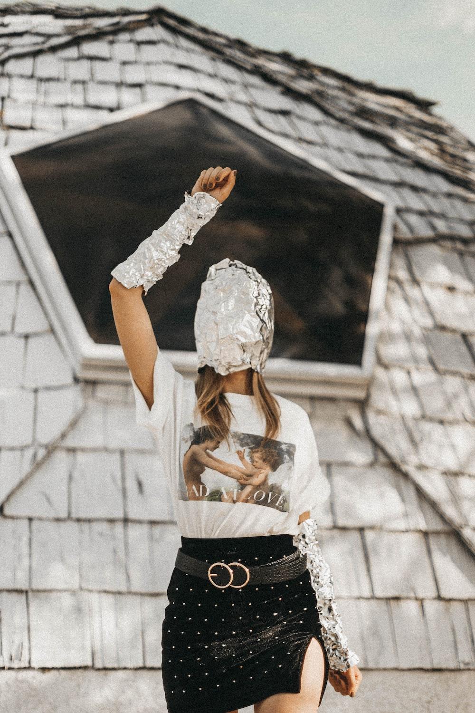 woman raising hand while standing near wall