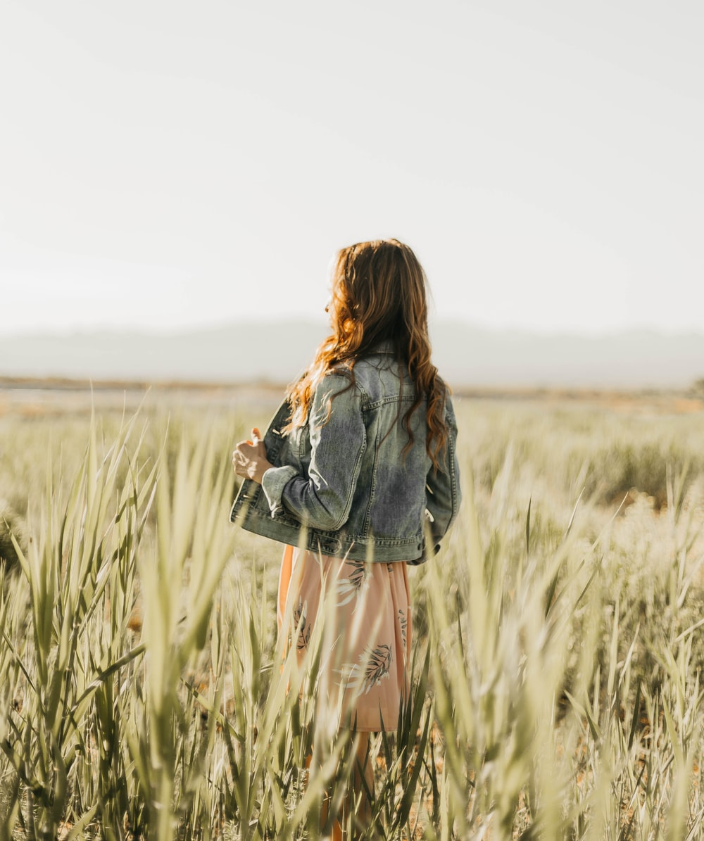 woman in grey denim jacket standing on grass field