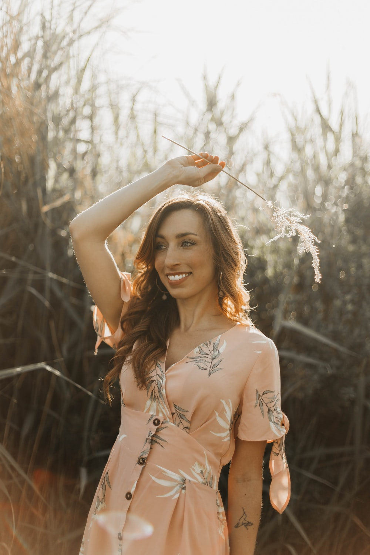 smiling woman standing near grass