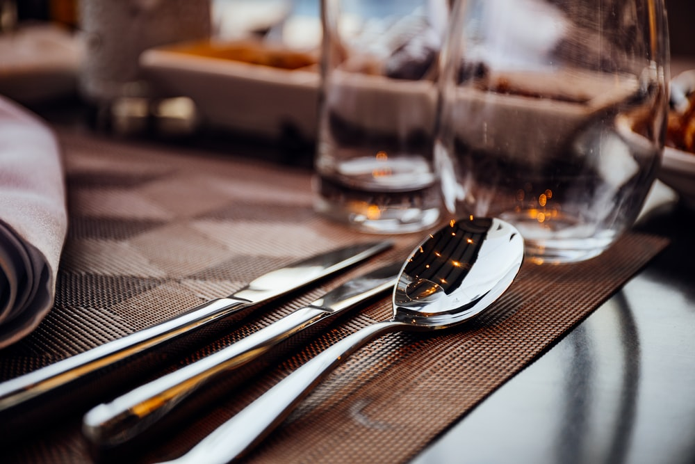 silver spoon and table knives on brown board