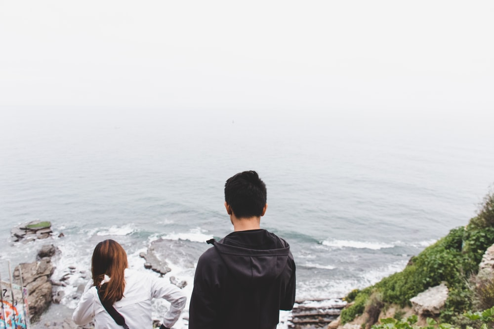 man and woman standing on cliff at daytime