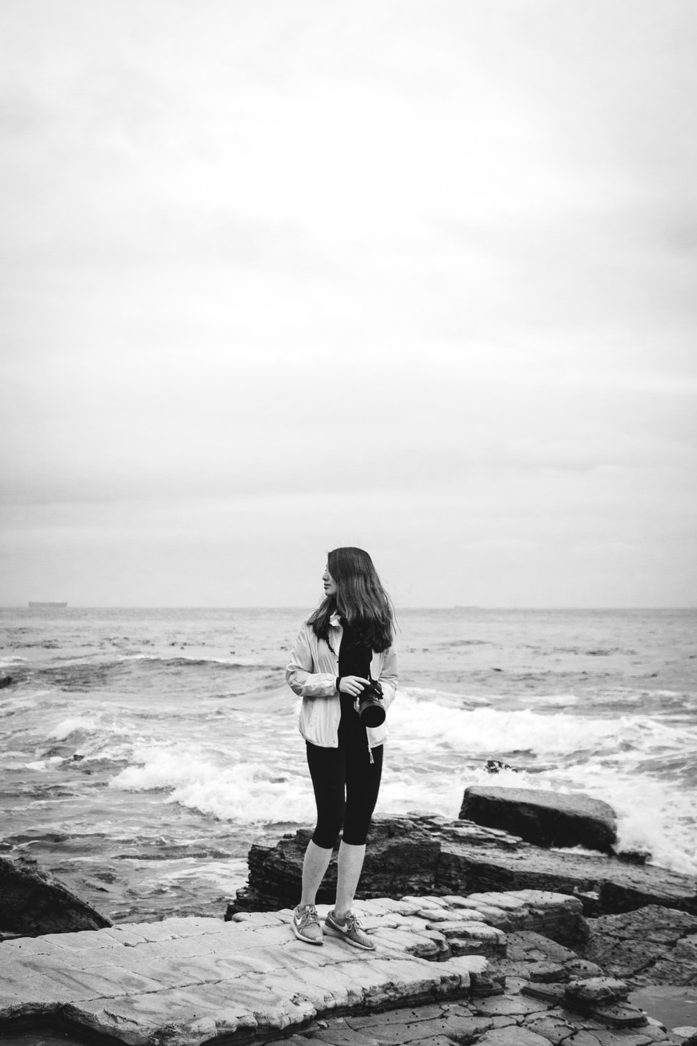 grayscale photography of woman holding camera by sea