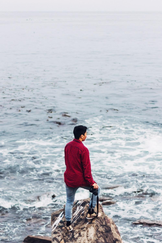 man wearing red dress shirt standing on seashore rock during daytime