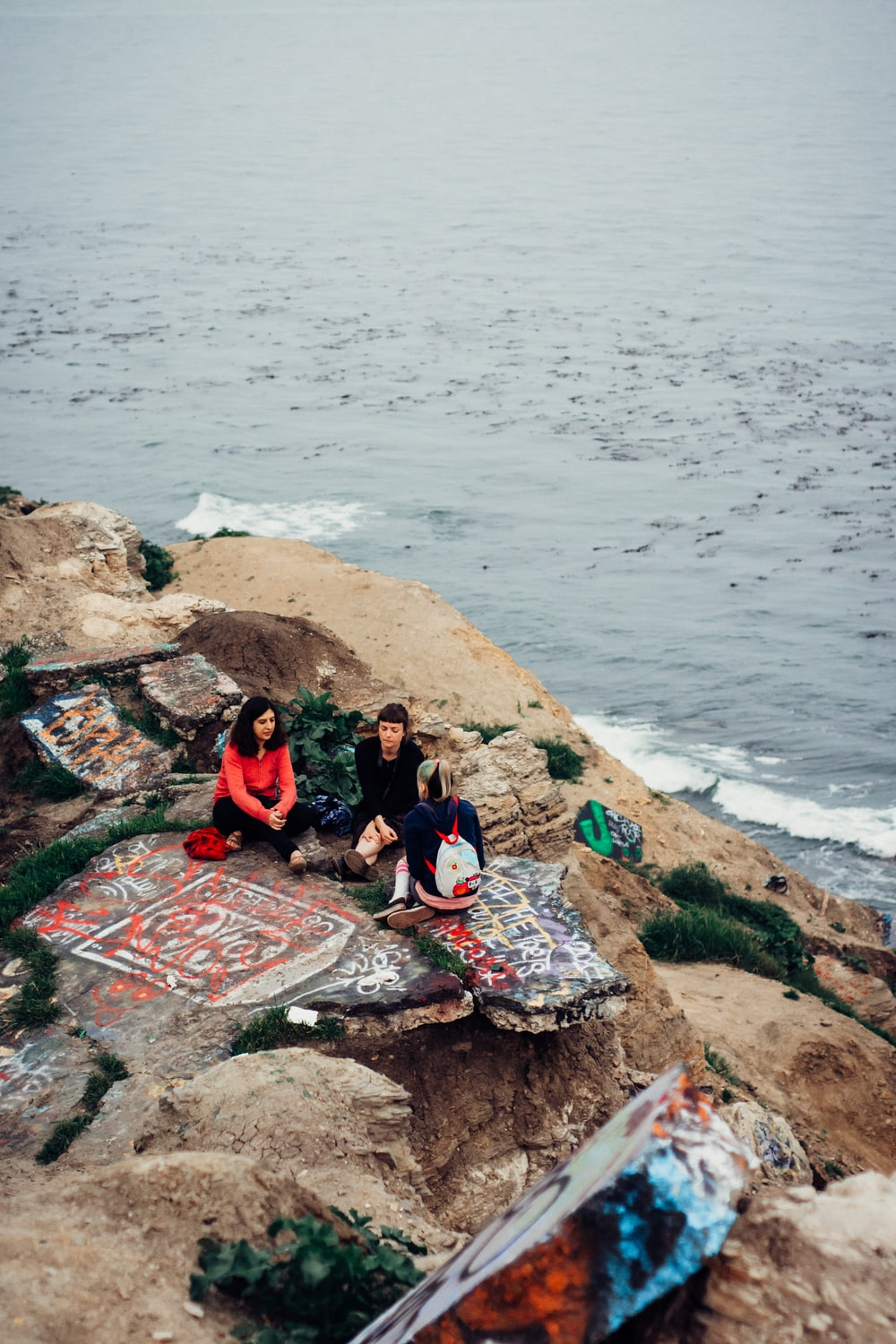 group of people sitting on rock formation beside sea