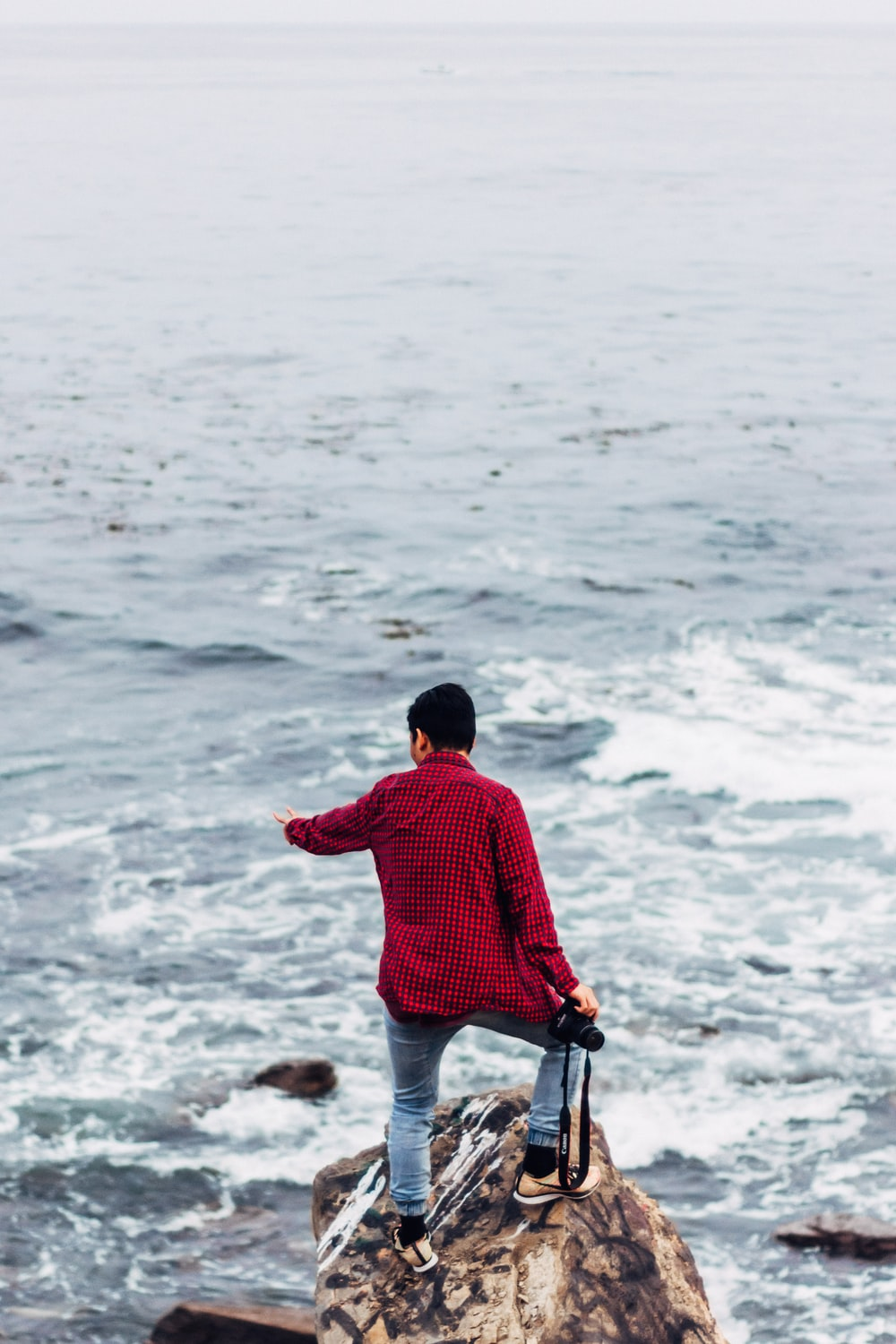 man holding DSLR camera standing on top of rock by sea