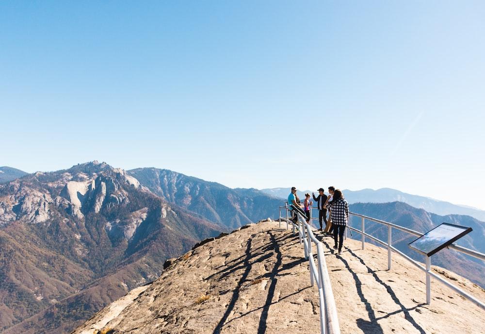 people standing between rails on mountain