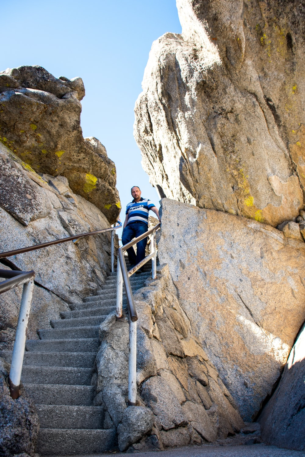 man walking going down from stairs beside big rocks