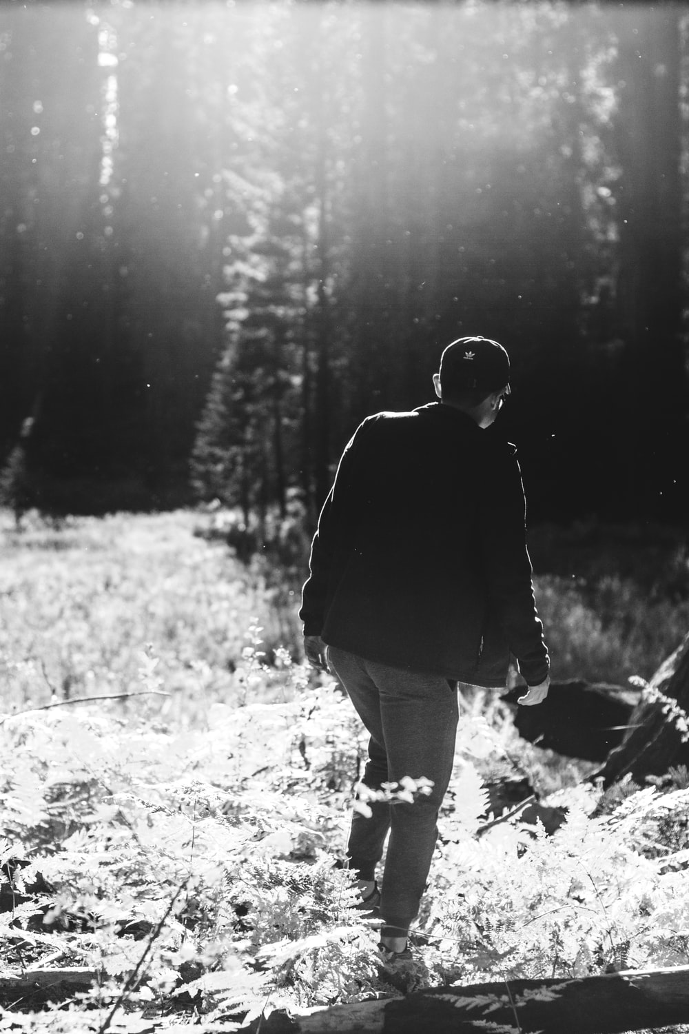 grayscale photo of man walking on forest