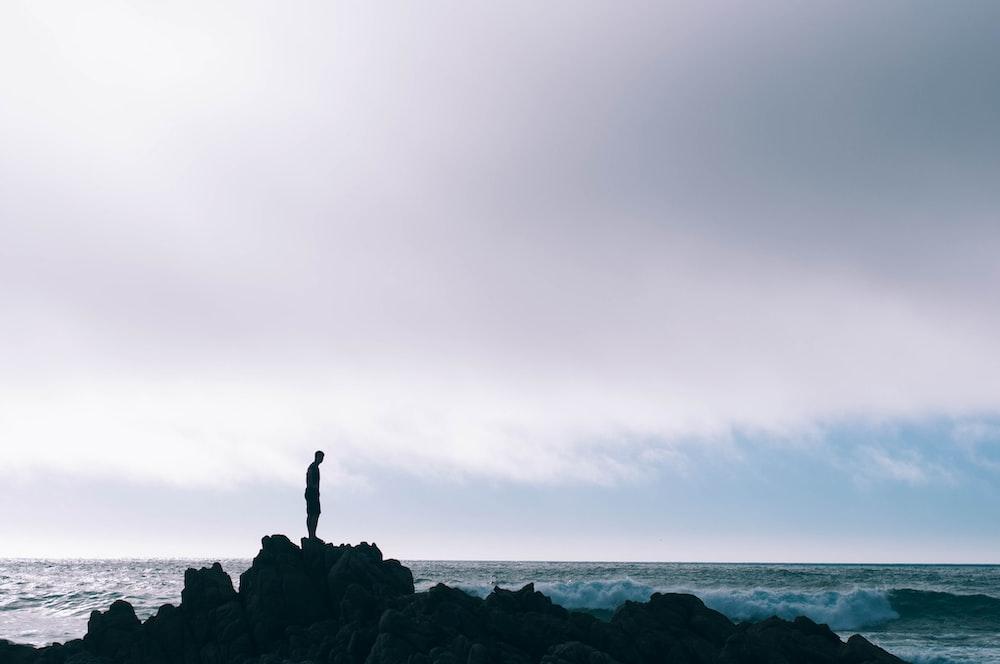 man standing on boulder in front of ocean
