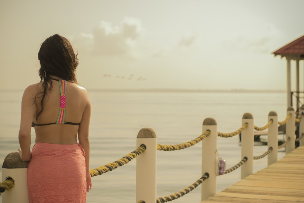 woman in pink skirt standing on boardwalk by the sea