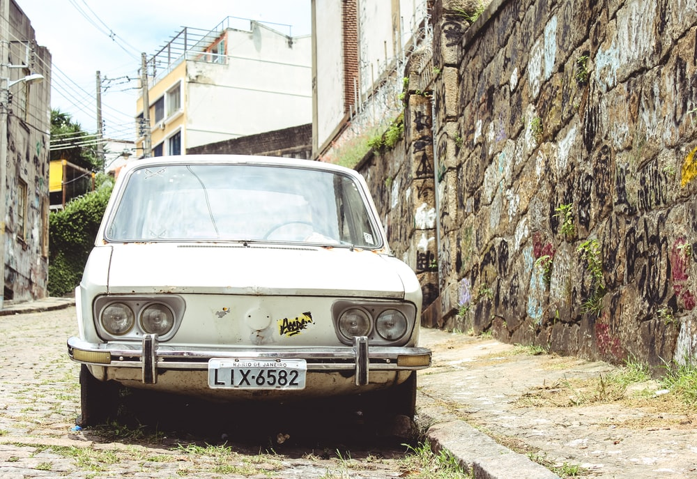white car beside wall
