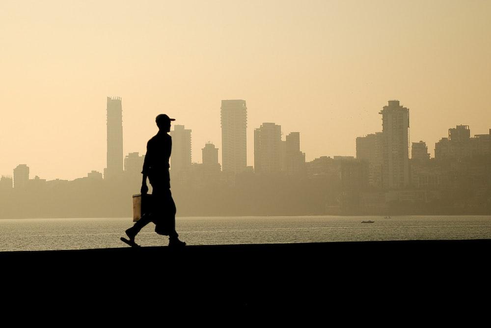 silhouette of man walking near the ocean