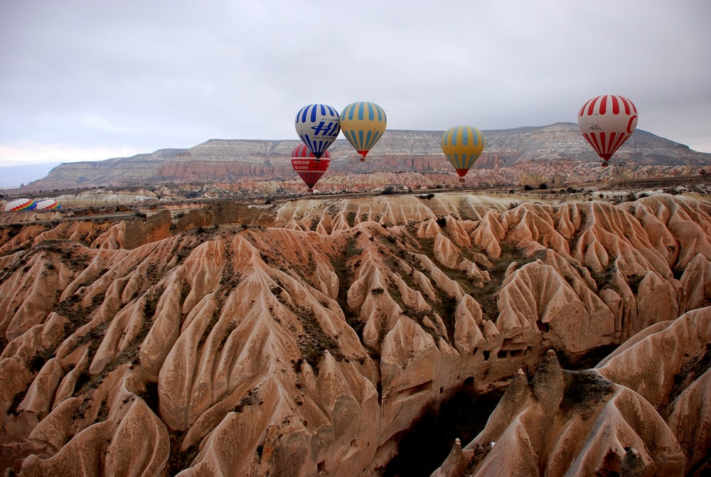 five hot air balloons floating over rock formation