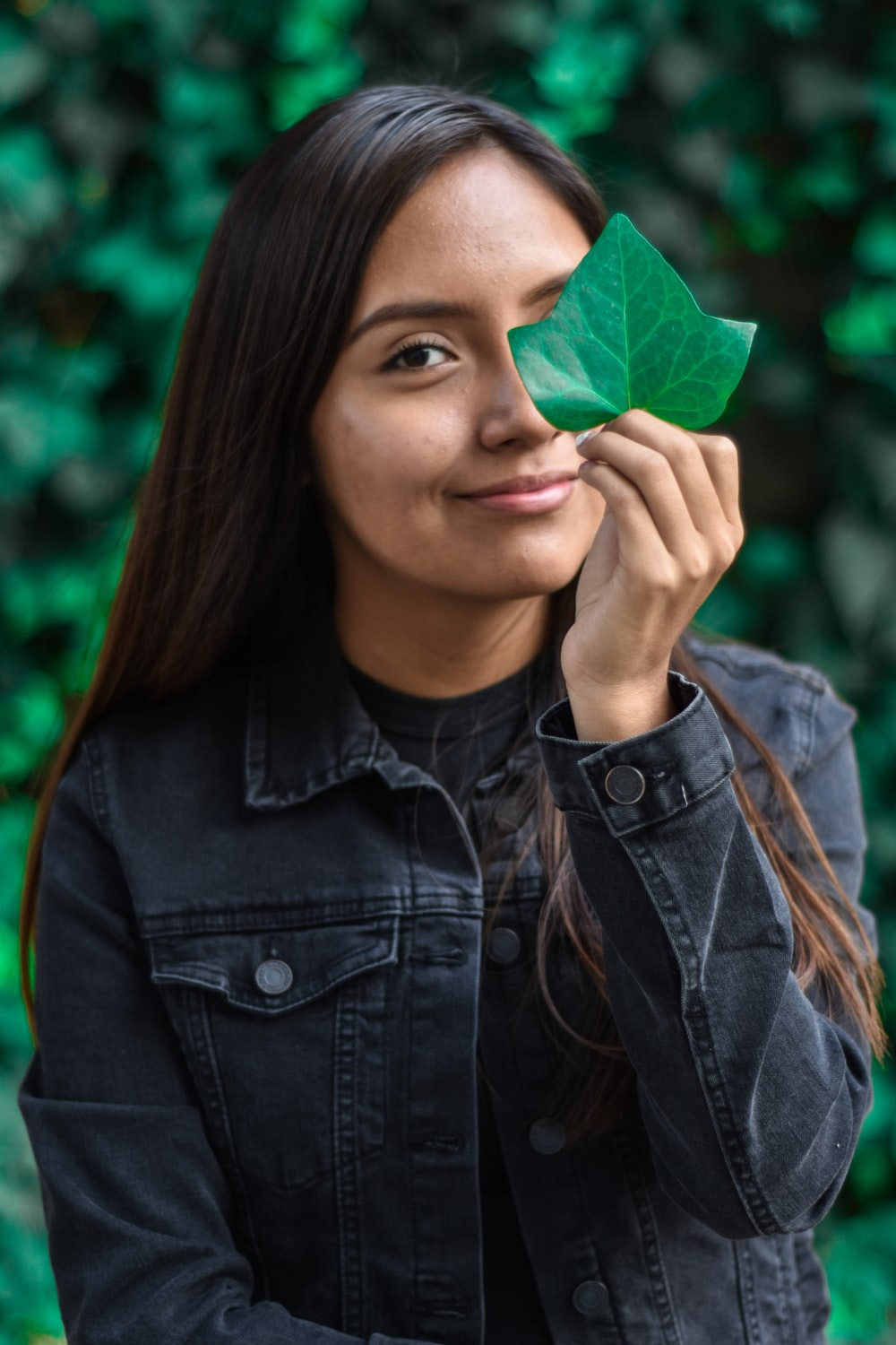 smiling woman holding green leaf