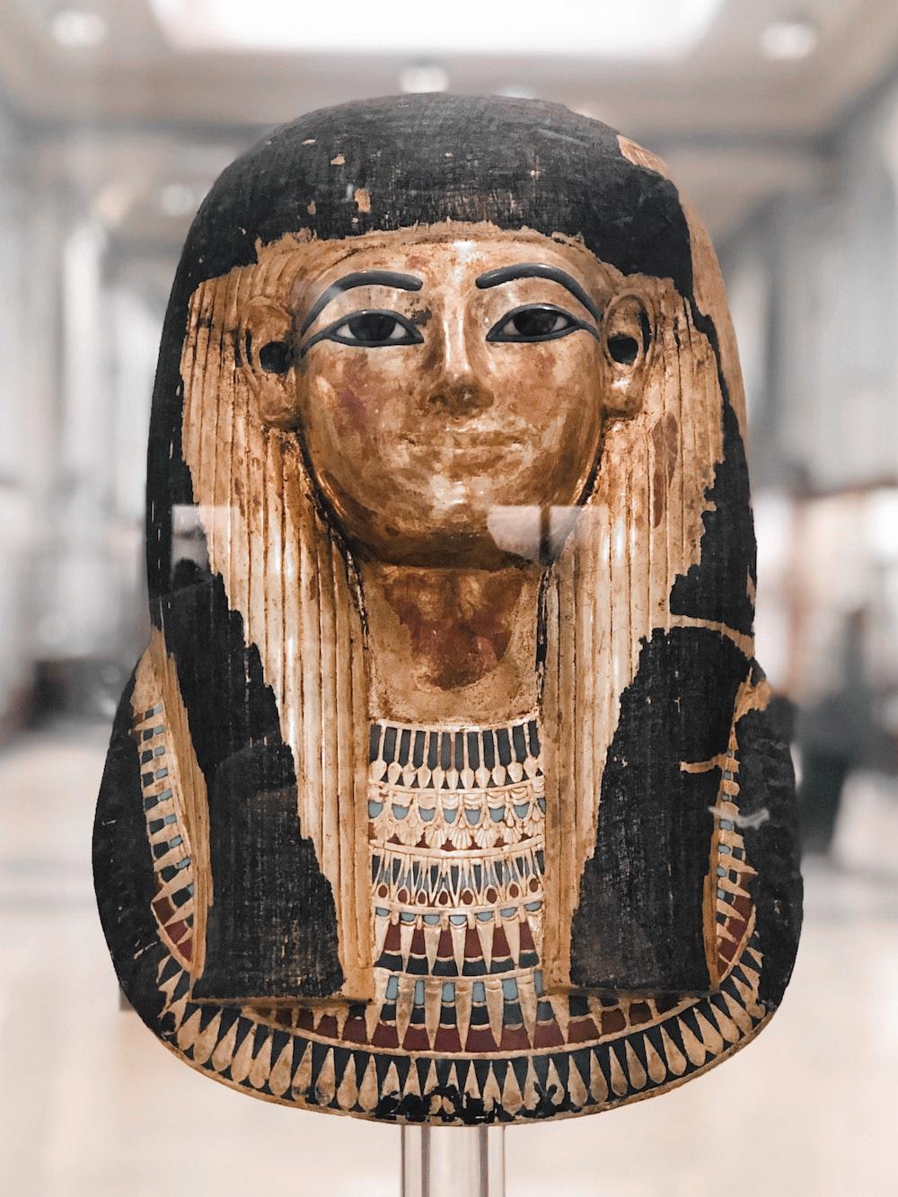 brown and black Egyptian pharaoh bust