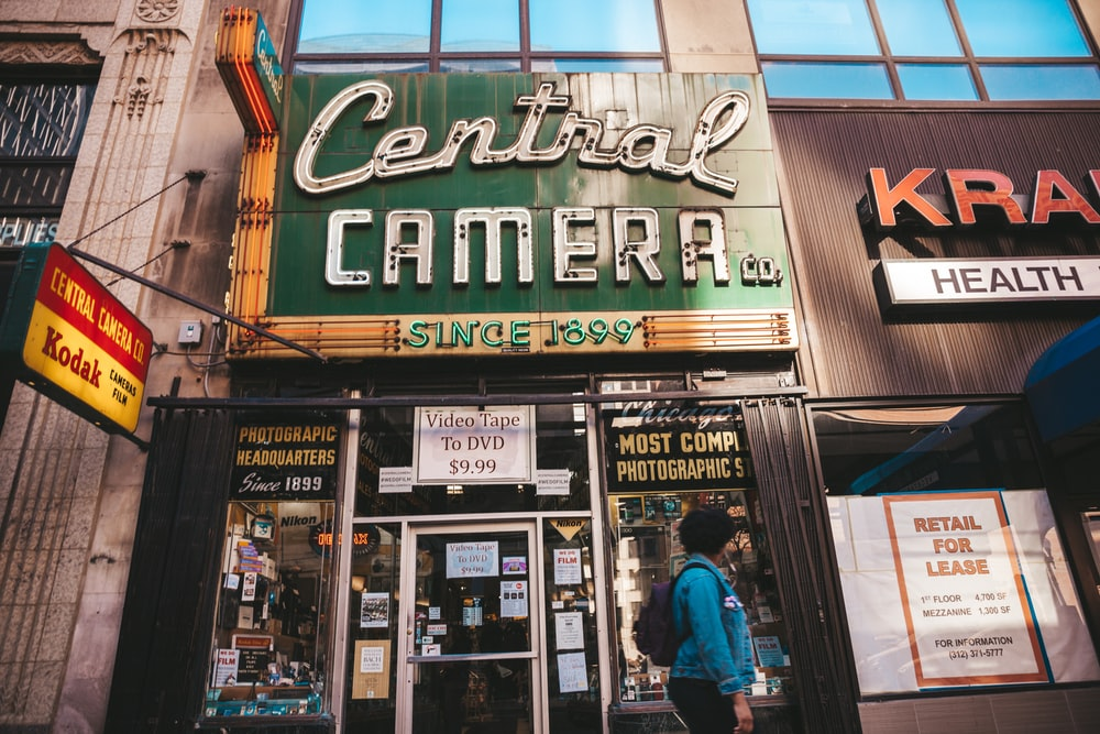 person standing beside Central Camera store-front