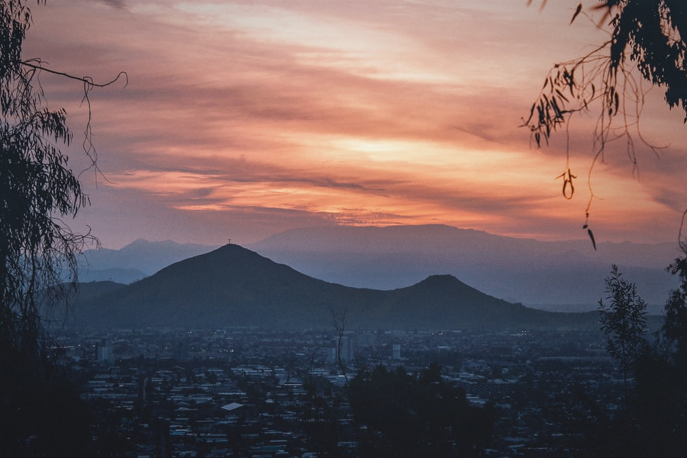 orange cloudy sunset sky over the city and mountains