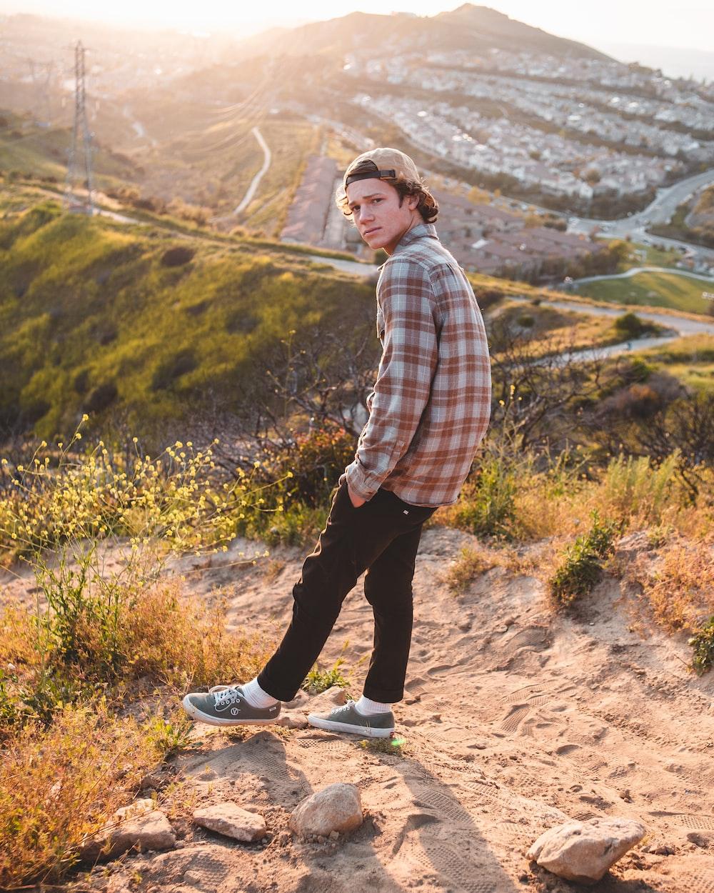 man wearing sport shirt standing on hill