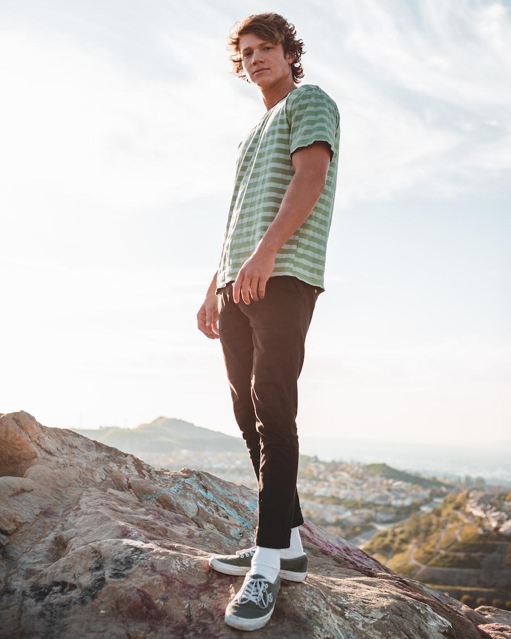man wearing t-shirt standing on rock
