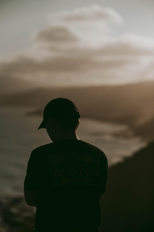 man in Burton shirt facing ocean