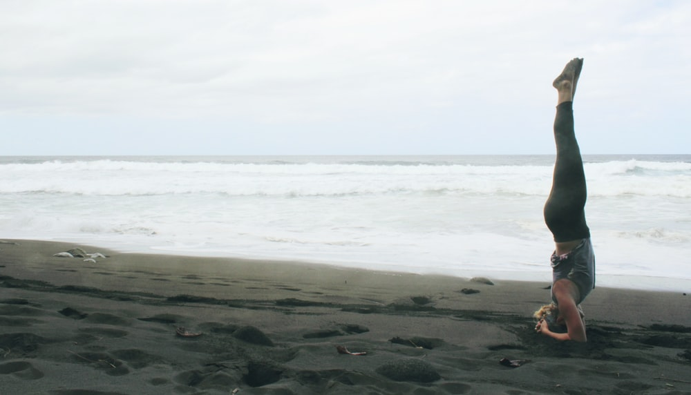 woman doing yoga exercise by inverting her body near seashore