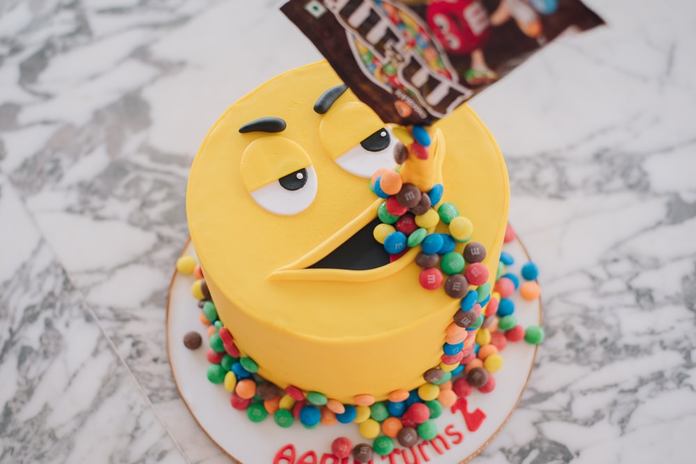 M&M pack pouring candies on M&m cake's mouth on marble surface