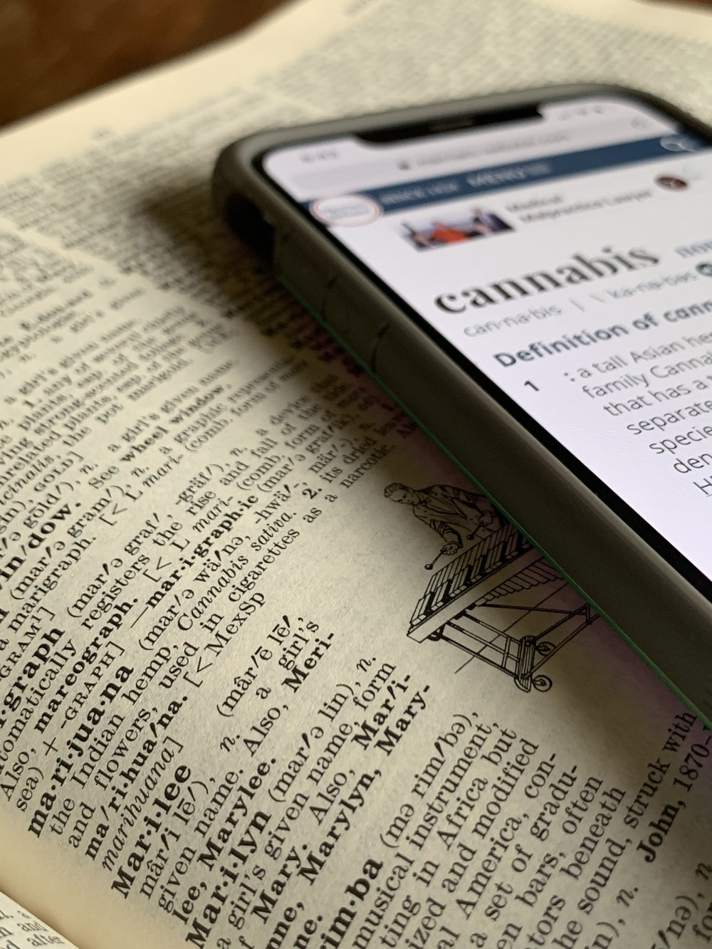 silver iPhone X displaying cannabis definition on top of dictionary